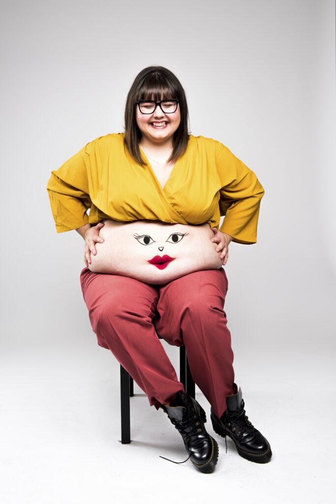 Credit Matt Crockett. Bild von Sofie Hagen, auf dem dicken Bauch ist ein lachendes Gesicht gemalt.